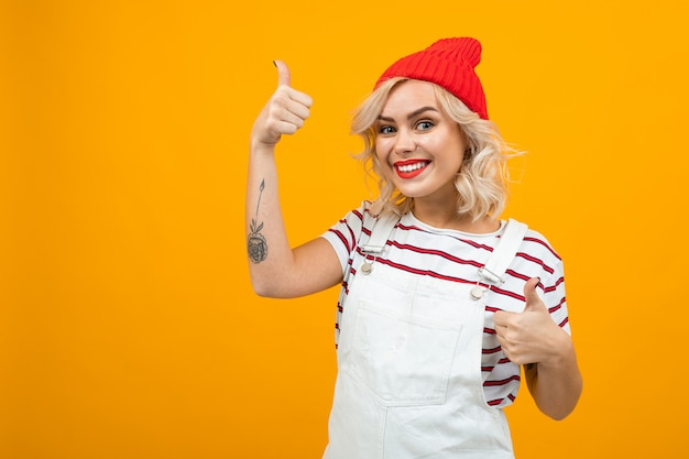 De mooie jonge vrouw met kort blond krullend haar en heldere make-up in witte overall en rode hoed houdt van iets en glimlacht, portret op sinaasappel wordt geïsoleerd die