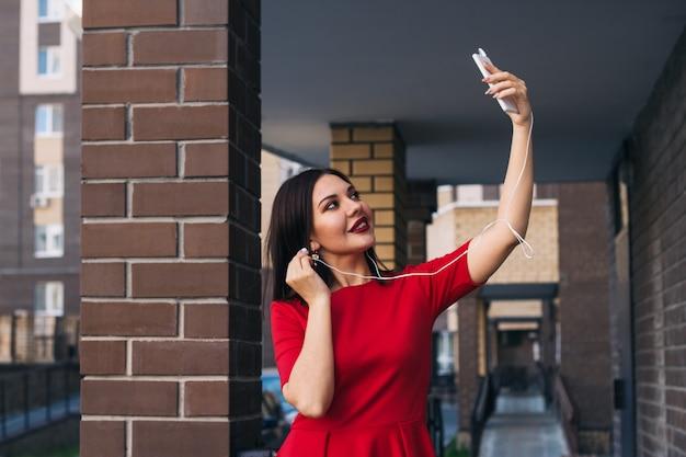 De mooie jonge vrouw met rode lippenstift in rode kleding gebruikt telefoon om selfie te nemen