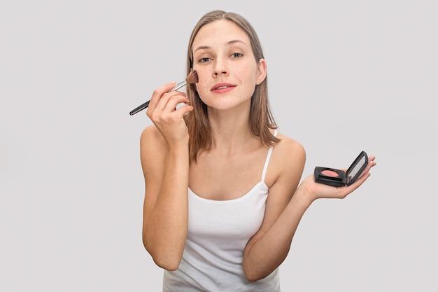 De mooie jonge vrouw met sproeten op gezicht stelt en kijkt. ze houdt pallete van rouge in een hand en poetst voor wangen in een andere. model is mooi.