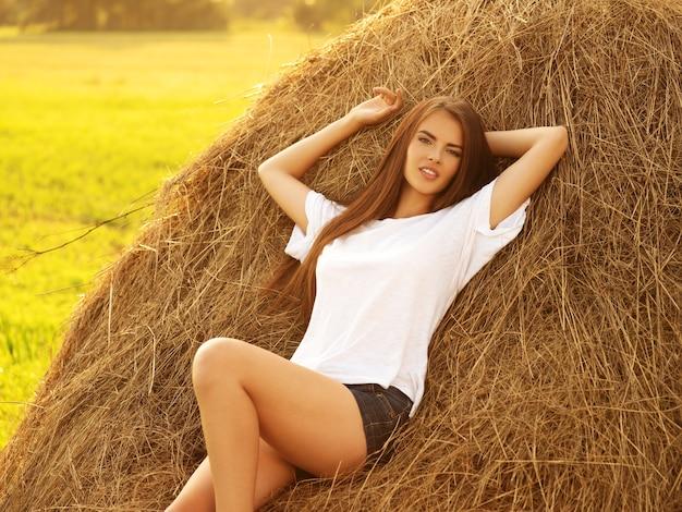 De mooie jonge vrouw ontspant op de hooiberg.