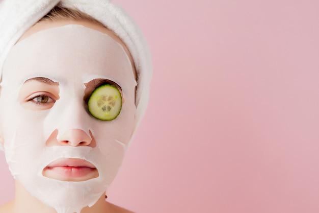 De mooie jonge vrouw past een kosmetisch weefselmasker op haar gezicht en een plak van komkommer toe