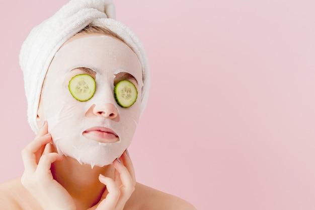 De mooie jonge vrouw past een kosmetisch weefselmasker toe op een gezicht met komkommer op roze.