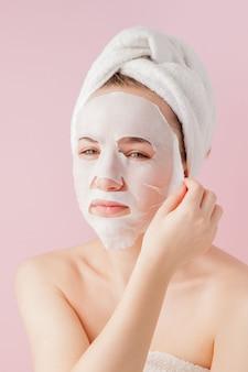 De mooie jonge vrouw past een kosmetisch weefselmasker toe op een gezicht op een roze muur. gezondheidszorg en schoonheidsbehandeling en technologieconcept.