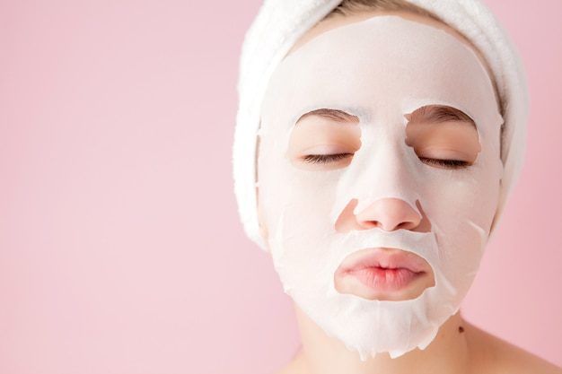 De mooie jonge vrouw past een kosmetisch weefselmasker toe op een gezicht op een roze