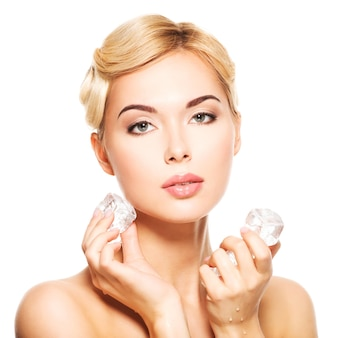 De mooie jonge vrouw past het ijs toe om onder ogen te zien. huid zorg concept. geïsoleerd op wit.