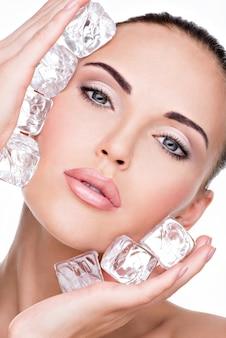 De mooie jonge vrouw past het ijs toe om onder ogen te zien. huid zorg concept.