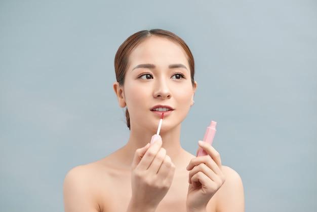 De mooie jonge vrouw past lipgloss toe. perfecte make-up. mooie lippen