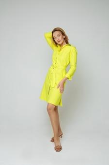 De mooie jonge vrouw stelt voor de camera in gele die kleding op witte ruimte wordt geïsoleerd