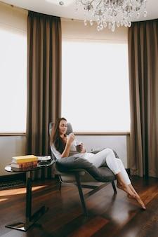 De mooie jonge vrouw thuis zittend op een moderne stoel voor het raam, ontspannen in haar woonkamer en koffie of thee drinken