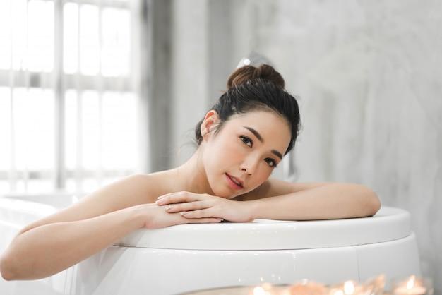 De mooie jonge vrouw van azië geniet van ontspannend nemend een bad met bellenschuim in badkuip bij de badkamers