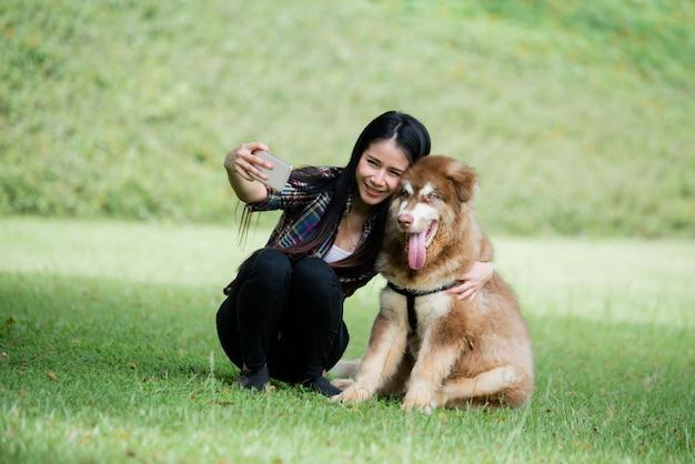 De mooie jonge vrouw vangt in openlucht foto met haar kleine hond in een park. levensstijl portret.