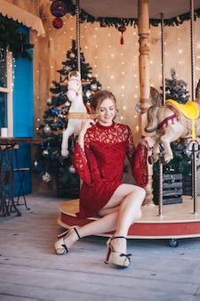 De mooie jonge vrouw verheugt zich dichtbij een carrousel met paarden. kerstmis.