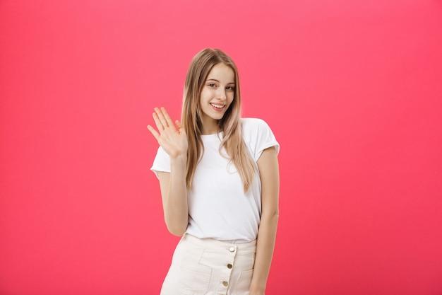 De mooie jonge vrouw zegt hallo geïsoleerd op roze achtergrond