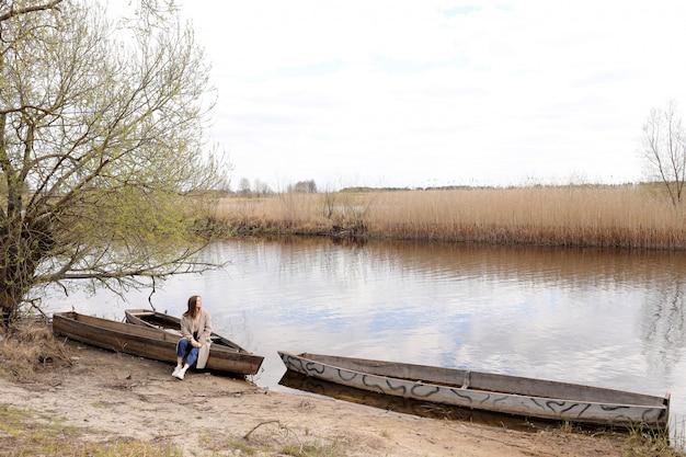 De mooie jonge vrouw zit en heeft pret in een boot dichtbij de rivier in de lentedag.