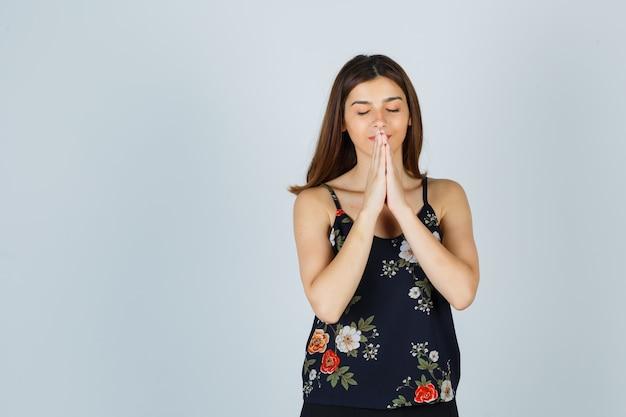 De mooie jonge vrouwelijke hand dient biddend gebaar in blouse in en kijkt hoopvol