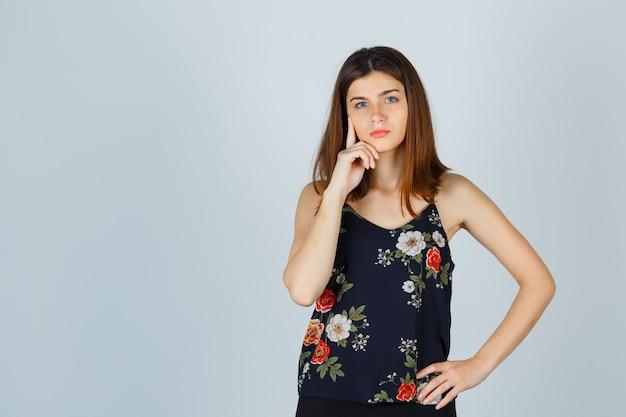 De mooie jonge vrouwelijke steunende kin dient blouse in en kijkt attent