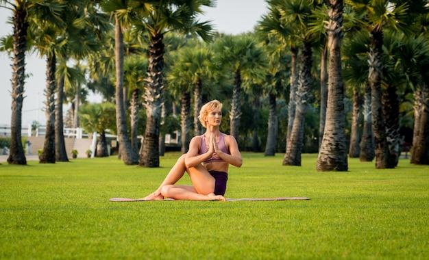 De mooie jonge yoga van vrouwenpraktijken bij het strand. ochtendtraining
