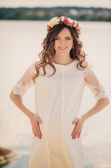De mooie jonge zwangere vrouw draagt witte kleding en bloemenkroon dichtbij het meer, de zomertijd, zwanger meisje. concept van moederschap