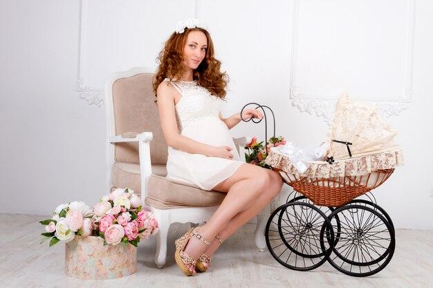 De mooie jonge zwangere vrouwentiener in witte kleding met kinderwagen zit op zachte klassieke stoel
