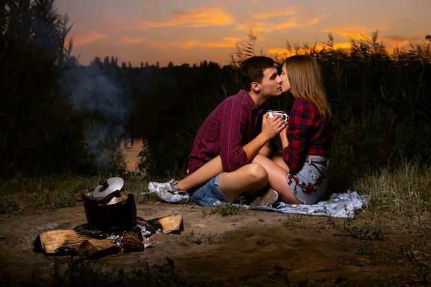 De mooie jongen en het meisje in rode geruite overhemden kussen dichtbij het vuur