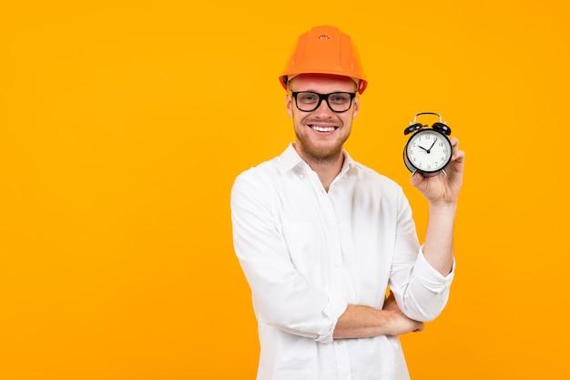 De mooie kaukasische ingenieursmens met glazen en oranje helm houdt een wekker die op geel wordt geïsoleerd