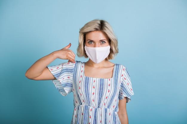 De mooie kaukasische vrouw die een kleding en een medisch masker draagt, bekijkt camera en gebaart de roepnaam