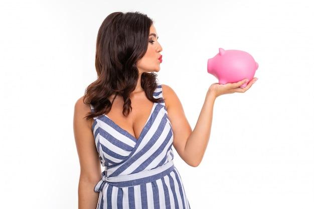 De mooie kaukasische vrouw houdt een roze die varken moneybox, beeld op wit wordt geïsoleerd