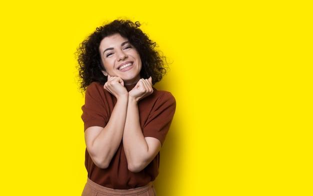 De mooie krullende haired vrouw glimlacht bij camera gebaren genoegen op een gele studiomuur