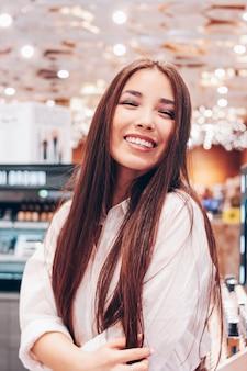De mooie lange jonge vrouw van het haar aziatische glimlachende meisje in winkelsupermarkt van schoonheidsmiddelen, vrije parfums,