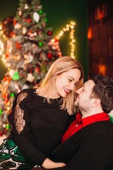 De mooie man en de vrouw genieten van de tijdzitting als zachte voorzitter vóór een kerstboom