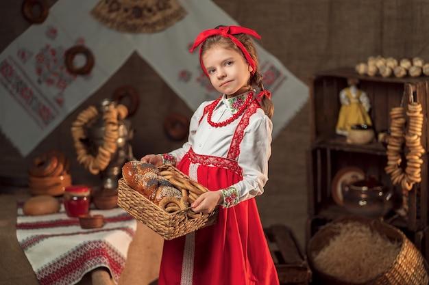 De mooie mand van de meisjesholding bagels en ander bakken in traditioneel huis die maslenitsa vieren