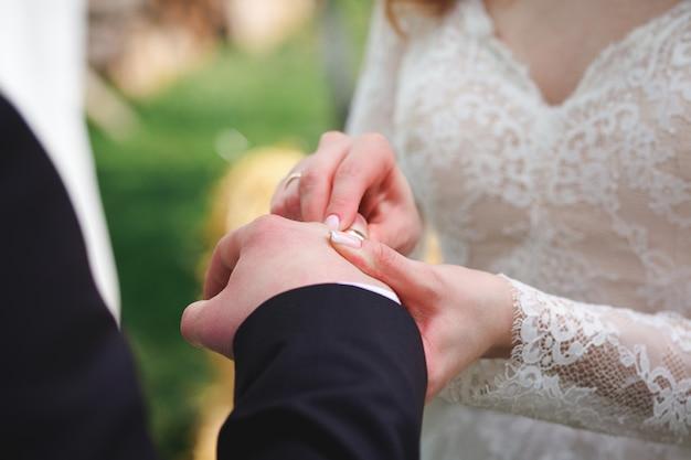 De mooie meisjesbruid in witte huwelijkskleding zet op de vinger van de bruidegom de gouden trouwring