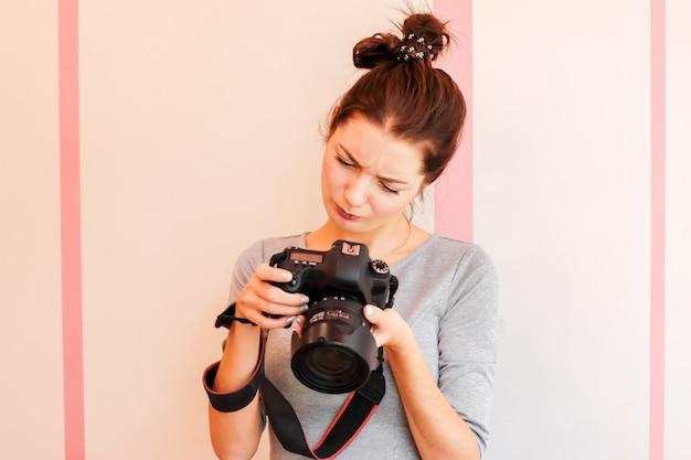 De mooie meisjesfotograaf onderzoekt haar camera en maakt grappige d