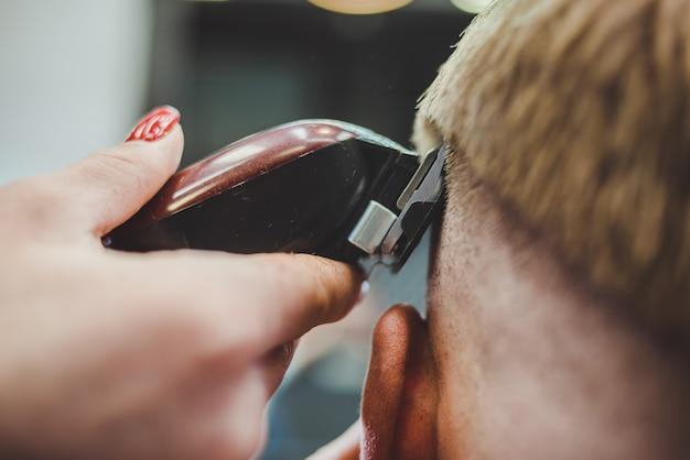 De mooie meisjeskapper snijdt een gebaarde man in de salon
