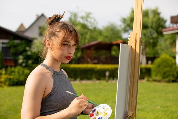 De mooie meisjeskunstenaar schildert
