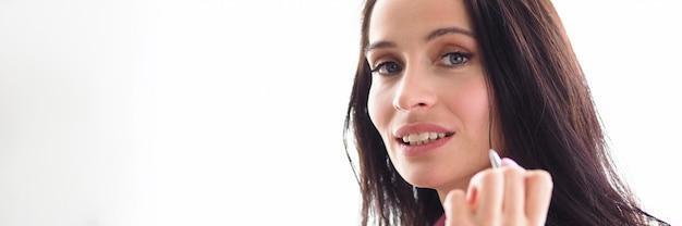 De mooie meisjesmanager houdt pengezicht en glimlacht