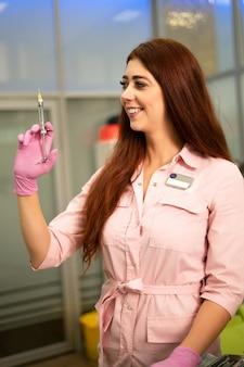 De mooie meisjestandarts houdt spuit in zijn hand. glimlachend en kijkend naar de camera. anesthesie en injecties in de tandheelkunde.