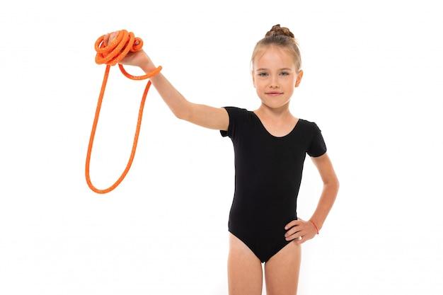 De mooie meisjesturner in legging doet sommige oefeningen op witte muur