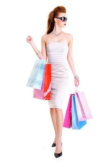 De mooie modieuze glamour vrouw met boodschappentassen in handen loopt in winkels