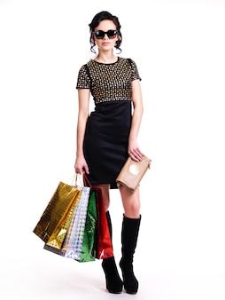 De mooie modieuze jonge vrouw in zwarte jurk en glazen met aankopen in handen - geïsoleerd op wit.
