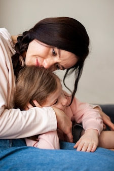 De mooie moeder die van de close-up haar dochter houdt