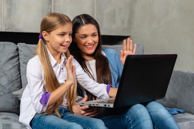 De mooie moeder en haar dochter hebben skype-vraag op laptop terwijl thuis het zitten