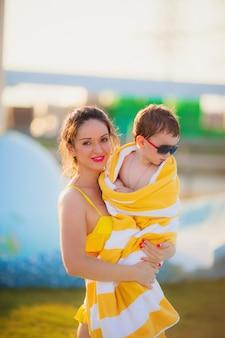 De mooie moeder in een geel badpak houdt in haar armen een zoon in zonnebril in in een gele handdoek op de achtergrond van het zwembad