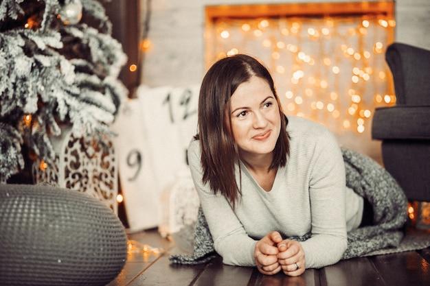 De mooie moeder ligt op de vloer vóór een kerstboom