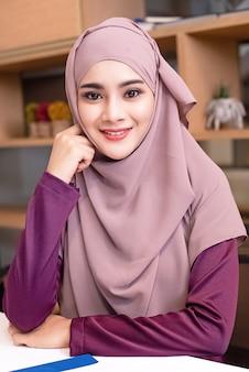 De mooie moslimvrouw die hijab draagt, legde hand op haar gezicht, met glimlach en gelukkig gevoel, portretmodel poseren, nieuwe generatie en slimme dame, wazig licht rond
