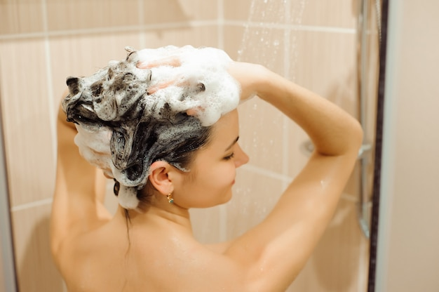 De mooie naakte jonge vrouw glimlacht en gebruikt shampoo terwijl t