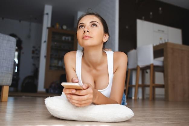 De mooie nadenkende jonge telefoon die van de vrouwenholding op de vloer in de woonkamer bepaalt