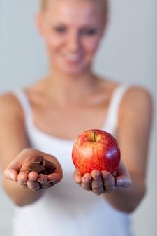 De mooie nadruk van de vrouwenholding chocolade en van de appel op appel