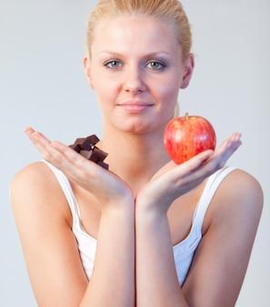 De mooie nadruk van de vrouwenholding chocolade en van de appel op vrouw