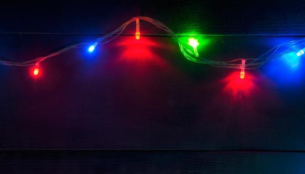 De mooie onscherpe kerst achtergrond met veel kleurrijke lampjes op het houten bureau